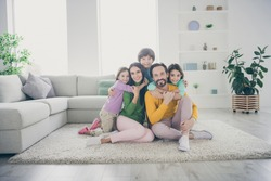Portrait of nice attractive adorable careful cheerful cheery family pre-teen kids mom dad sitting on carpet floor embracing at cozy comfortable light white interior style house apartment living-room