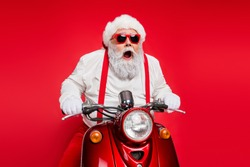 Portrait of nice attractive bearded crazy cheerful cheery funny funky Santa riding motor bike delivering shop orders hurry up isolated over bright vivid shine vibrant red color background