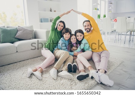 Portrait of nice attractive careful cheerful adorable ideal family three pre-teen kids mom dad sitting on carpet floor showing making roof good change at cozy comfort light white interior style house