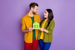 Portrait of nice attractive glad cheerful cheery friends friendship holding in hands green house form sale bank loan purchase isolated bright vivid shine vibrant lilac violet purple color background
