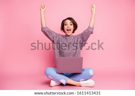 Portrait of nice attractive lovely charming cheerful cheery brown-haired girl sitting in lotus pose using laptop rising hands up celebrating attainment isolated over pink pastel color background