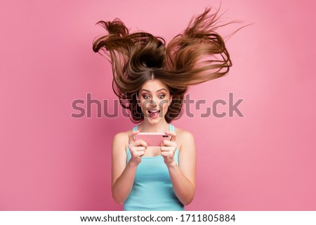 Portrait of nice attractive lovely charming funny focused cheerful cheery straight-haired girl using cell having fun free time ideal silky hair flying isolated on pink pastel color background