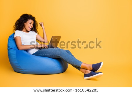 Portrait of nice attractive lovely cheerful cheery glad satisfied wavy-haired girl sitting in bag chair using laptop celebrating isolated over bright vivid shine vibrant yellow color background