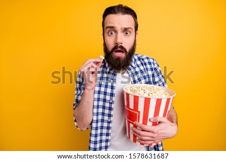 Portrait of nice attractive worried scared addicted bearded guy in checked shirt overeating popcorn junk snack watching scary video isolated over bright vivid shine vibrant yellow color background