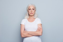 Portrait  of nice, charming, aged, perfect, nice, pretty, concentrated, woman with folded hands, serious expression, looking at camera,  standing over gray background