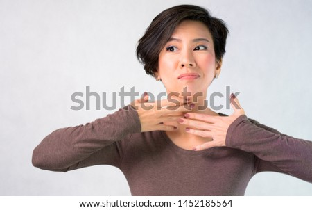 Portrait of nice charming attractive middle aged asian woman worried  about aging neck wrinkles, she cover with her hands. Anti-aging, Face self-massage, Beauty skin care, Signs of aging concept.