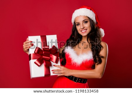 Portrait of nice charming pretty adorable positive cheerful curly-haired lady in hat, getting, holding gift box, isolated over bright vivid red background