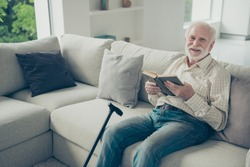 Portrait of nice cheerful cheery dreamy stylish old man wearing checked shirt sitting on divan holding in hands book in white light modern interior
