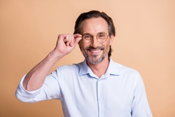 Portrait of nice cheerful content smart man wearing touching specs isolated over beige pastel color background