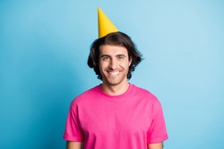 Portrait of nice cheerful guy wearing yellow celebratory cap corporate event isolated over bright blue color background
