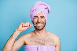Portrait of nice cheerful healthy guy wearing turban towel brushing teeth anti caries isolated on bright blue color background