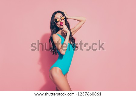 Portrait of nice cool trendy stylish lovely adorable charming glamorous attractive slim fit thin wavy-haired lady licking yummy sugary lolly pop red lips eyeglasses eyewear isolated on pink background