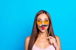 Portrait of nice cool winsome adorable positive optimistic straight-haired girl wearing tanktop and yellow sun glasses, sending air kiss, trying fake mustache, isolated on bright vivid blue background