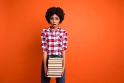 Portrait of nice cute attractive smart clever intelligent wavy-haired lady wearing checked shirt carrying holding many different book isolated over bright vivid shine orange background