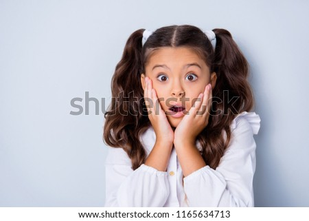 Portrait of nice cute tender adorable lovely stylish girl with curly ponytails in white formal blouse shirt, showing amazement gesture, palms to cheeks. Isolated over grey background