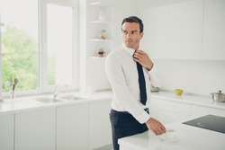 Portrait of nice elegant classy attractive handsome candid man business shark drinking cacao before work day fixing tie at light modern interior kitchen