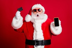 Portrait of nice handsome amazed stunned bearded Santa holding in hand plastic card device web app shop buy order delivery pay wireless payment isolated bright vivid shine vibrant red color background