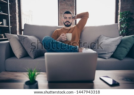 Portrait of nice handsome stylish trendy student hipster hold hand have mug espresso look read feel satisfied tv television use user device dressed sit divan orange denim jeans sweater pullover