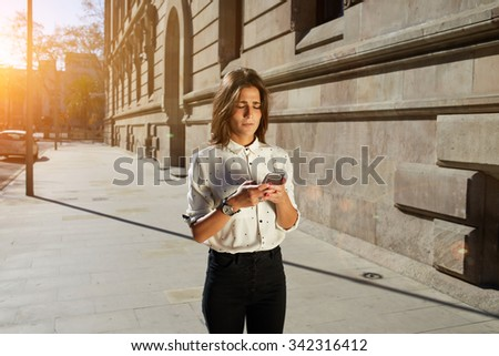 Portrait of nice hipster girl typing text message on her smart phone, young female using cellular phone while strolling in the city, woman using telephone with copy space area and your text message #342316412