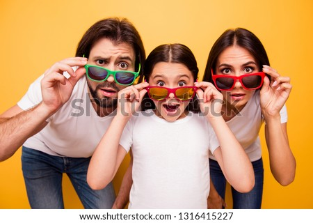 Portrait of nice lovely attractive cheerful amazed people having fun day wearing colorful modern eyewear omg gesture isolated over shine vivid pastel yellow background