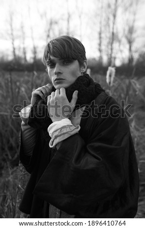 Portrait of nice male model. Nature background. Autumn forest. Cold weather. Black and white photo. Modern fashion. Unisex. Pastel colors. Strange eclectic clothes. Mix of historical and boho styles.  Photo stock ©
