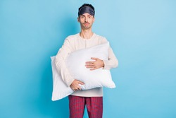Portrait of nice miserable guy wearing sleep clothes holding in hands pillow isolated over bright blue color background