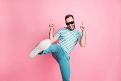 Portrait of nice naughty cheerful funky guy dancing having fun wear sunglasses showing sole isolated over pink pastel color background