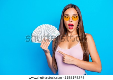 Portrait of nice sweet tender alluring attractive adorable winsome straight-haired girl wearing yellow sunglasses, tanktop, opened mouth, showing fan of usd, isolated on bright vivid blue background