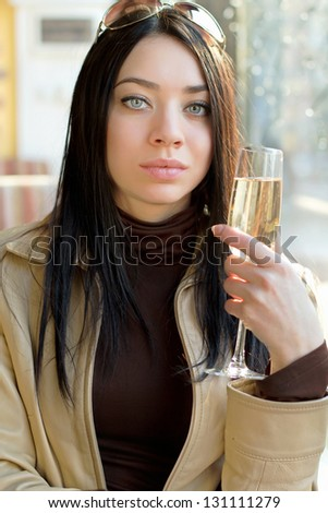 Portrait of nice young brunette with a glass of champagne. Isolated on white