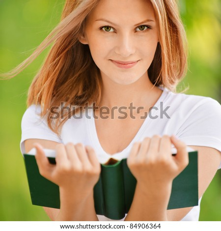 Portrait of nice young smiling woman with book on green background of city park.