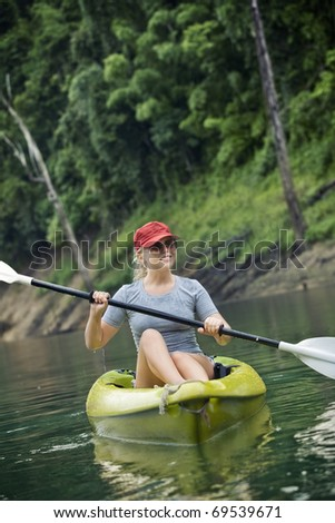 Portrait of nice young woman paddling kayak in summer  environment