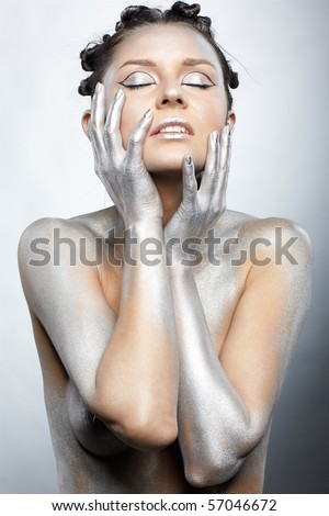 portrait of nude girl body painted with silver posing on gray