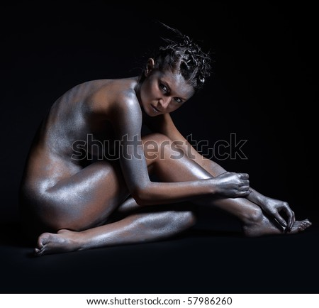 portrait of nude girl body painted with silver sitting on black