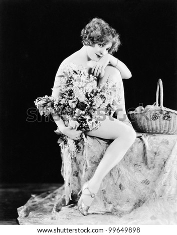 Portrait of nude woman holding flowers