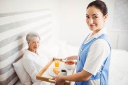 Portrait of nurse giving breakfast to senior woman in bedroom