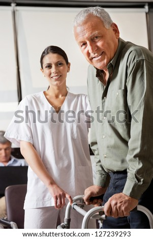 Portrait of nurse helping senior male patient to use walker with person sitting in background