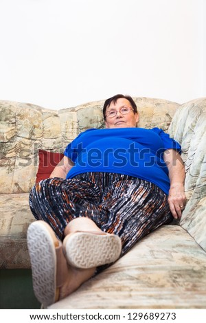 Portrait of obese elderly woman lying on sofa.