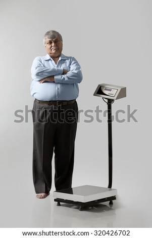Portrait of obese man with weighing scale