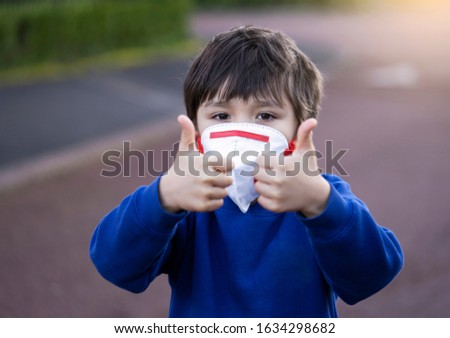Portrait of of School kid wearing protective face mask for pollution or virus, Child in school uniform wearing medical face mask and showing thumbs up while waiting for school bus in the morning.