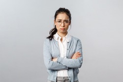 Portrait of offended insecure and timid cute asian girl complaining on cruel customer being rude to her, cross hands over chest defensive and upset, frowning gloomy, feel upset grey background
