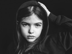 portrait of offended sad young girl on dark background, black and white photo, concept of problems of parents and children