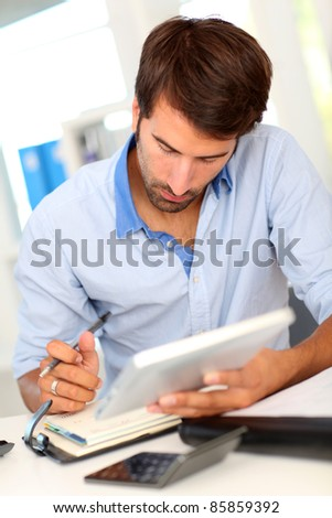 Portrait of office worker using electronic tablet