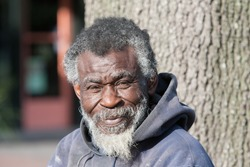 Portrait of old african american homeless man in black in white outdoors.
