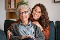 Portrait of old grandma and adult granddaughter hugging with love on sofa while looking at camera. Happy young woman with eyeglasses hugging from behind older grandma with spectacles generation family