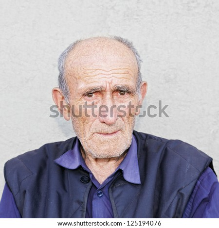 Portrait of old hoary man in blue shirt