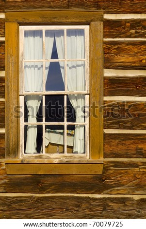 Portrait of old log cabin window with square log detail and chinking