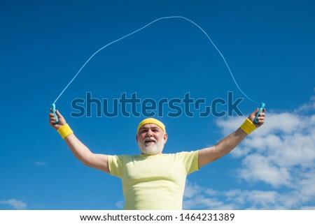 Portrait of old male senior sportsman skipping rope