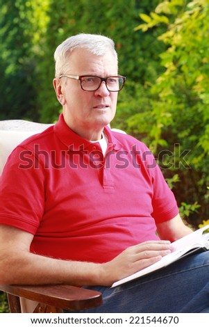 Portrait of old man sitting at garden at home and reading book.