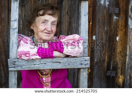 Portrait of old smiling woman in ethnic clothes in the village.
