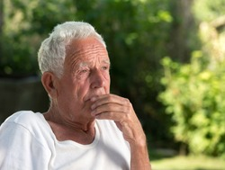 Portrait of old thoughtful man in park with green background. Senior care and depression concept